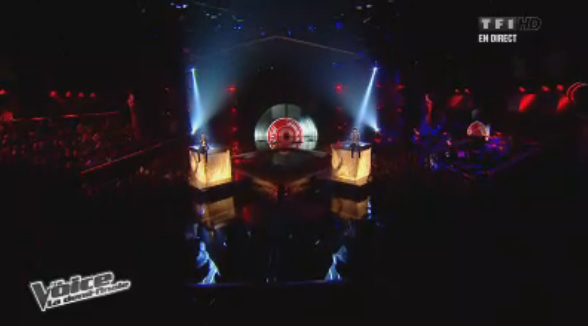 Pour leur duel, Olympe et Anthony Touma sont assis sur des cubes sur fond de grand 45 tours !