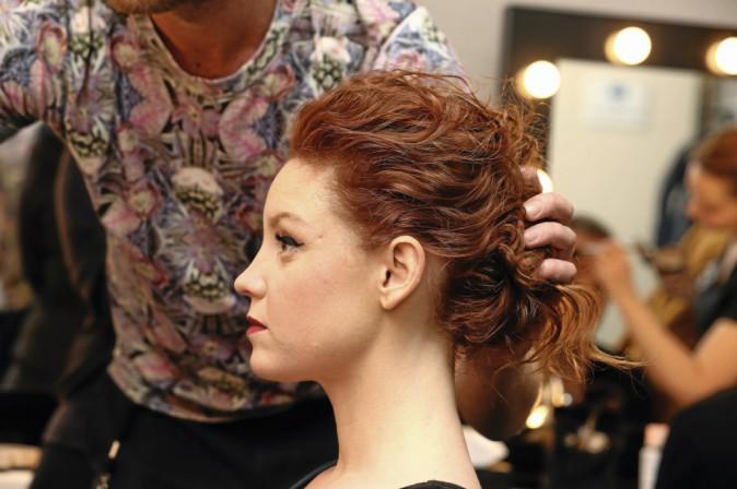 4 >> Fixez Isolez les cheveux du dessus de la tête. Avec des pinces à chignon, relevez les mèches une à une pour les fixer vers le milieu de...