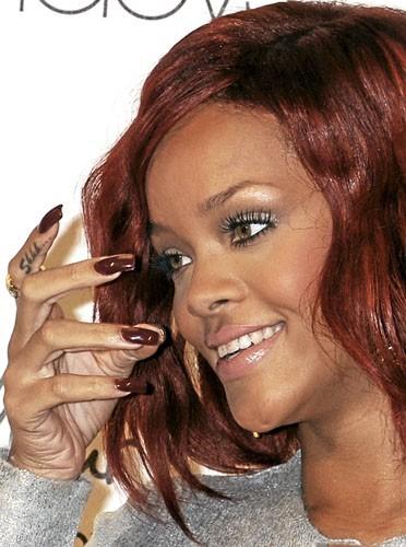 La chanteuse de la Barbade assortit le rouge de ses cheveux à sa manucure. Canon !
