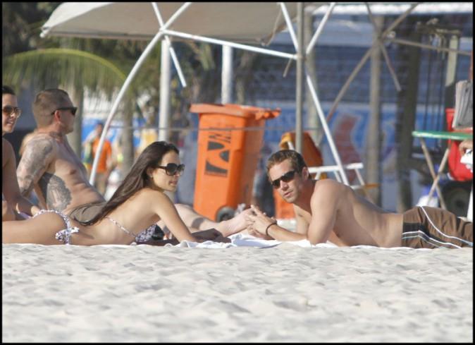Paul Walker les mains dans le sable et les yeux dans l'eau avec sa petite amie de l'époque