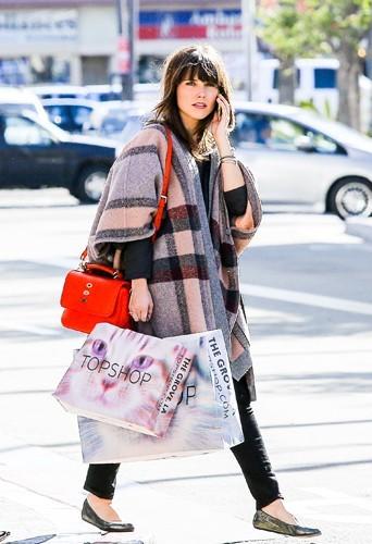Quand elle a les mains pleines à la sortie d'une séance shopping, pas de panique ! Elle porte son sac en bandoulière !