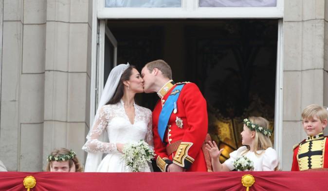 Premier baiser public du couple marié, au dessus de la foule de Buckingham Palace
