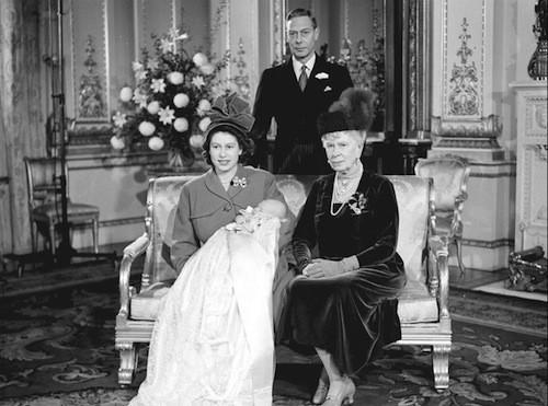 Le prince Charles dans les bras d'Elizabeth II. Son père Philip se tient derrière.