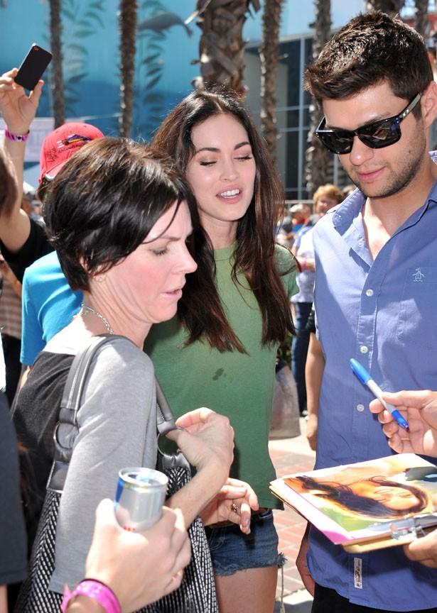 Elle en profite pour signer des autographes...