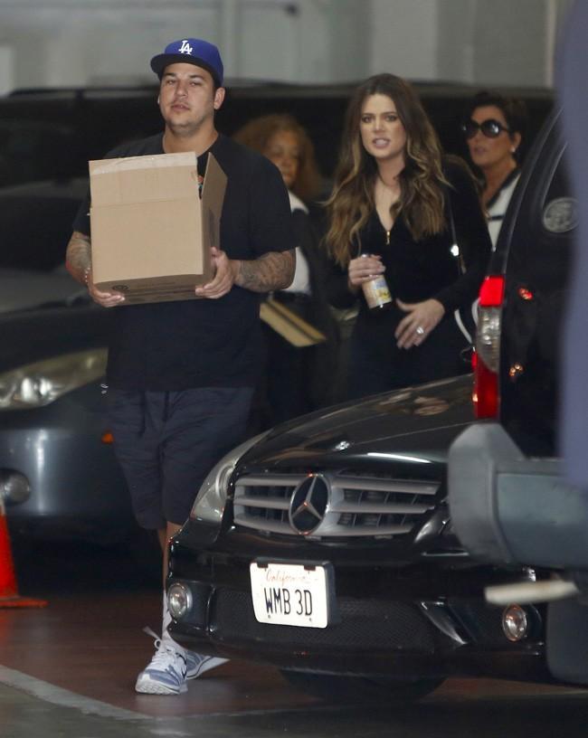 Rob Kardashian avec son carton de chaussettes, sa soeur Khloé et leur mère Kris, à Los Angeles le 6 juin 2013
