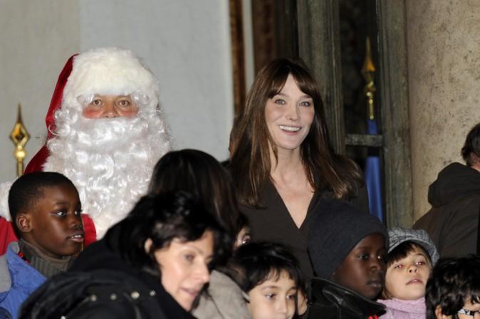 Carla Bruni Sarkozy, le père Noël et des enfants attendant leurs cadeaux au Palais de l'Élysée en décembre 2008